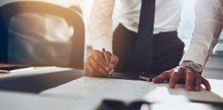 Ein Mann unterschreibt einen Anstellungsvertrag