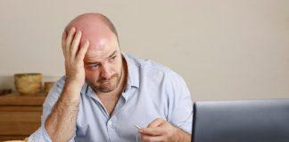Ein Mann sitzt besorgt vor dem Laptop, er hat Bewerbungsangst